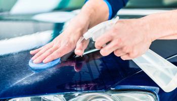 Happy young man looking at camera while waxing a blue car outdoors at car wash