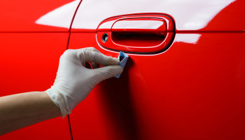 Car detailing series : Closeup of hand coating red car paint